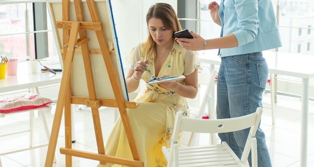 Concept d'école d'art, de créativité et de loisirs - étudiante ou jeune artiste avec chevalet, palette et peinture au pinceau en studio. le professeur l'aide