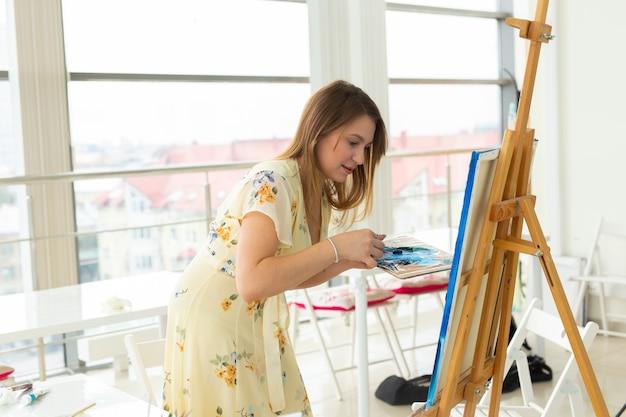 Concept d'école d'art, de créativité et de loisirs - étudiante ou jeune artiste avec chevalet, palette et peinture au pinceau en studio