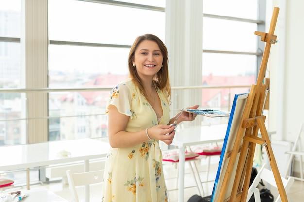 Concept d'école d'art, de créativité et de loisirs - étudiante ou jeune artiste avec chevalet, palette et peinture au pinceau en studio.