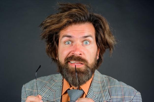 Concept d'école bouchent portrait d'un enseignant confus homme barbu en costume d'école de concept d'éducation