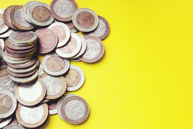 Concept d'économie d'argent financier. photo en gros plan de pièces d'argent en métal sur fond jaune