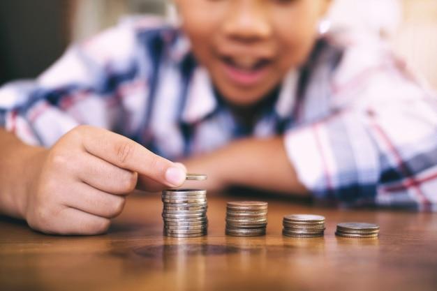 Concept d'économie d'argent. kid compter l'argent et faire pile de pièces.