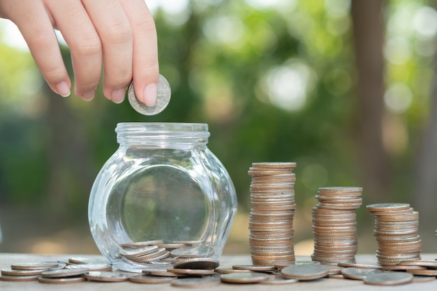Concept d'économie d'argent prédéfini par la main masculine mettant la pile de pièces d'argent en pleine croissance. disposez les pièces en tas avec les mains, content de l'argent.