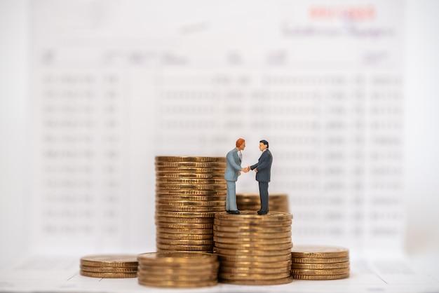 Concept d'économie d'argent et de travail. deux hommes d'affaires figurines miniatures poignardent et font trembler la main sur la pile de pièces d'or sur le livret de banque.