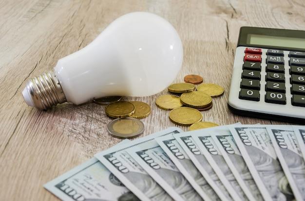 Concept d'économie d'énergie une ampoule avec une calculatrice et de l'argent