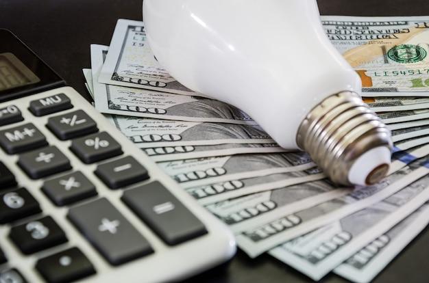 Concept d'économie d'énergie ampoule avec calculatrice et dollars sur fond noir