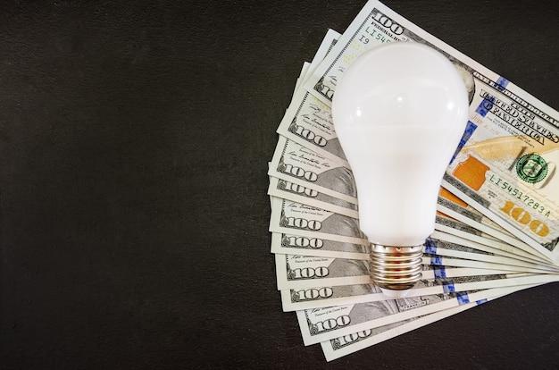 Concept d'économie d'énergie ampoule et dollars sur fond noir