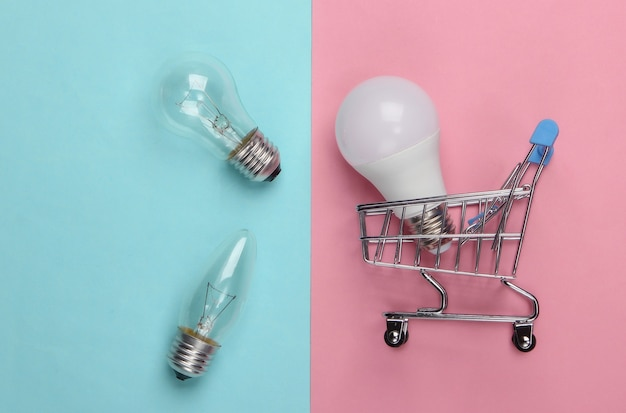 Concept d'économie d'énergie. chariot de supermarché et ampoules sur pastel bleu rose
