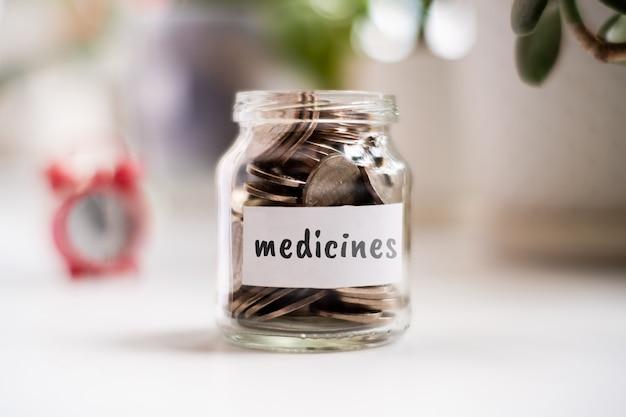 Concept d'économies sur les médicaments - bocal en verre avec des pièces et une inscription.
