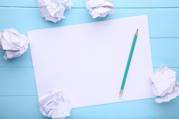 Concept d'écriture - bourres de papier froissées avec une feuille de papier blanc et un crayon sur du bois bleu