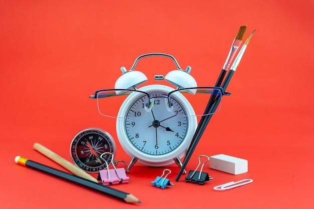 Concept education ou affaires réveil et lunettes de professeur objets commerciaux isolés sur coloré