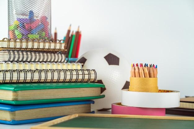 Concept de l'éducation. crayons de couleur dans un porte-crayon et des fournitures scolaires sur tableau blanc