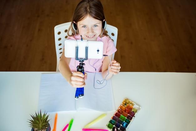 Concept d'éducation à distance. confinement lié au covid. une fille caucasienne apprend à dessiner en ligne pendant l'auto-isolement