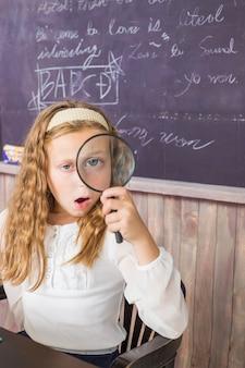 Concept d'éducation et d'école petite fille avec loupe à l'école écolière assise dans la classe...
