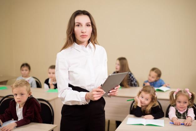Concept d'éducation, d'école primaire, d'apprentissage et de personnes. enseignant et élèves en arrière-plan.