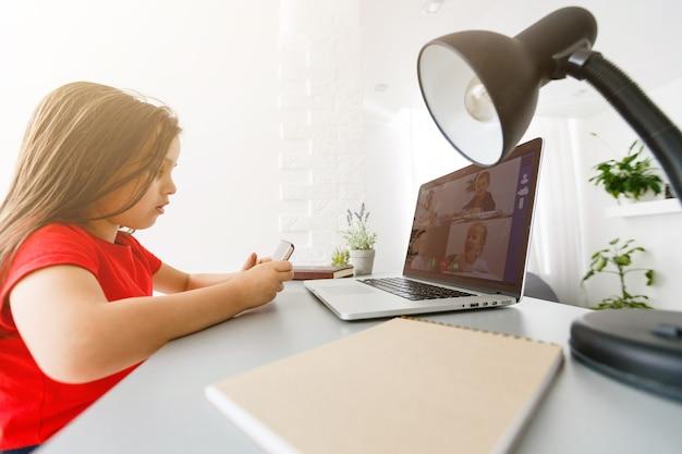 Concept d'éducation, d'école, de technologie et d'internet - petite étudiante avec smartphone à la maison