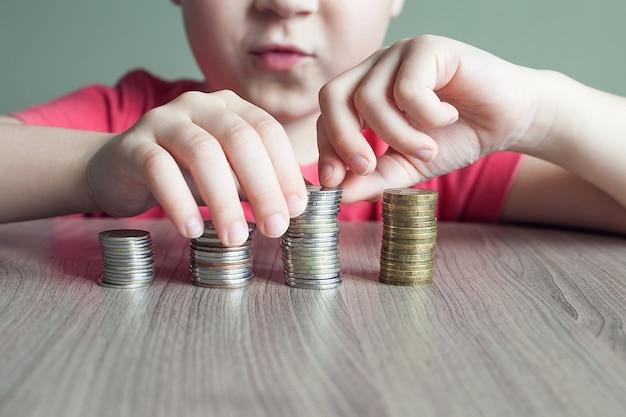 Le concept d'éducation économique des enfants. garçon construit une tour à l'aide de pièces de monnaie.
