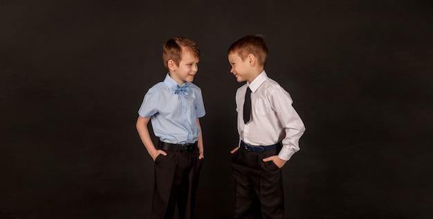 Concept d'éducation, d'éducation, d'amitié masculine et de fraternité. deux petits frères et amis garçons élégants, parlant et heureux ensemble, sur fond noir. portrait de 2 mecs vers le même but