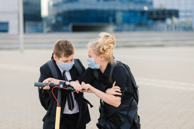 Concept d'éducation, d'enfance et de personnes. heureux les écoliers avec des sacs à dos et des scooters à l'extérieur dans un masque de protection