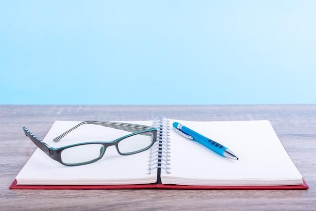 Concept éducation ou entreprise : journal ouvert ou carnet de notes avec des lunettes modernes et un stylo bleu posé sur la table en bois isolée sur fond bleu.