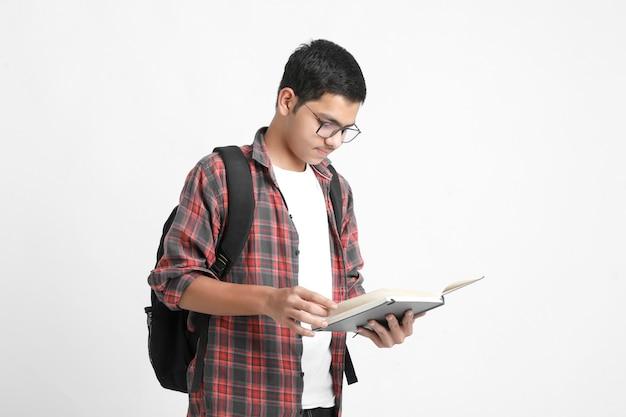 Concept de l'éducation: étudiant indien tenant un sac et livre de lecture sur fond blanc