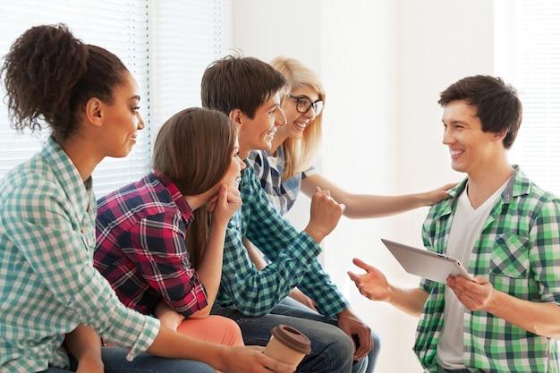 Concept d'éducation - étudiants communiquant et riant à l'école