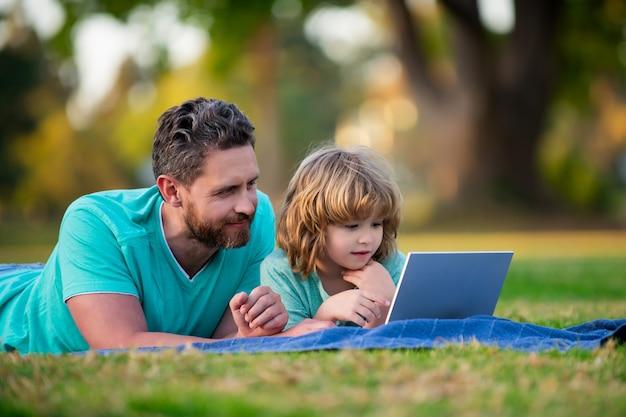 Concept d'éducation familiale père enseignant à son fils comment utiliser un ordinateur portable