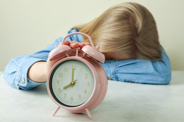 Concept d'éducation avec une fille fatiguée et un réveil