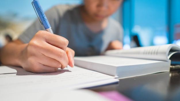 Concept de l'éducation. gros plan de la main d'un étudiant tenant un stylo et écrit sur papier