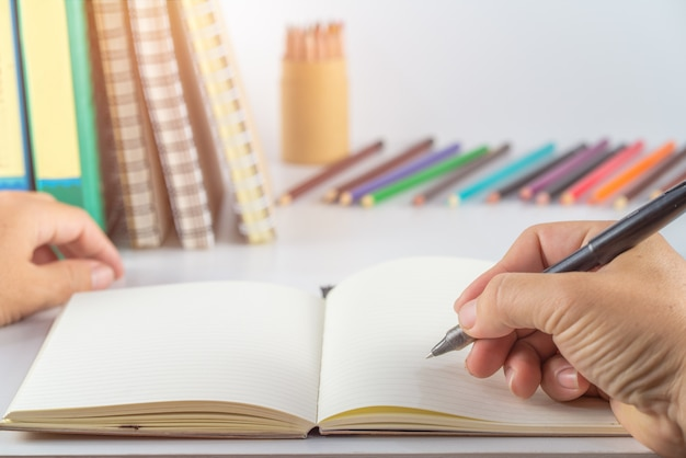 Concept de l'éducation. homme main écrire cahier et fournitures scolaires sur table