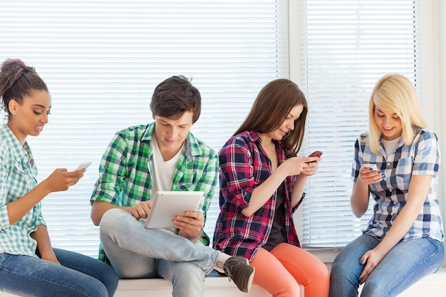Concept d'éducation et d'internet - étudiants regardant leurs téléphones et tablettes à l'école