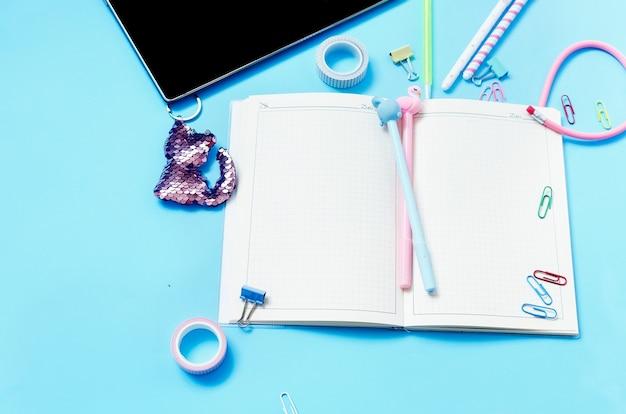 Concept d'éducation en ligne tablette téléphone écouteurs cahier fournitures scolaires sur bleu