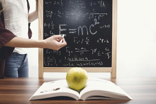 Concept de l'éducation, livre et pomme dans le fond du tableau noir