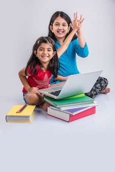 Concept d'éducation à la maison - 2 jolies petites filles indiennes ou asiatiques ludiques qui étudient ou font leurs devoirs sur un ordinateur portable sur une pile de livres tout en étant assises par terre à la maison. isolé sur fond blanc