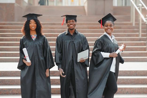 Concept d'éducation, d'obtention du diplôme et de personnes - groupe d'étudiants internationaux heureux dans des conseils de mortier et des robes de baccalauréat avec des diplômes
