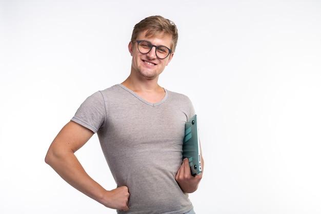 Concept d'éducation et de personnes. bel homme étudiant à lunettes ressemble à heureux avec un ordinateur portable sur blanc