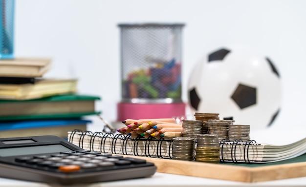 Concept de l'éducation. pièce d'argent et calculatrice avec fournitures scolaires sur tableau blanc