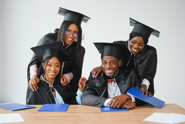 Concept d'éducation, de remise des diplômes et de personnes - groupe d'étudiants diplômés internationaux heureux en panneaux de mortier et robes de baccalauréat avec diplômes