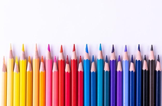 Concept d'éducation ou de retour à l'école. divers crayons de couleur isolés sur blanc.