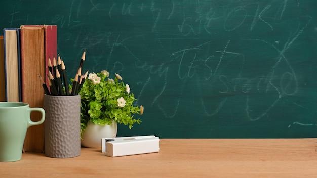 Concept d'éducation ou de retour à l'école. livres, crayons, tasse, écurie blanche, plante sur planche de bois sur fond de tableau vert.
