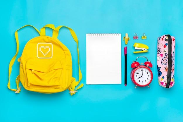 Concept d'éducation de retour à l'école sac à dos jaune avec fournitures scolaires stylos pour cahier pinces ciseaux