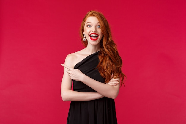 Concept d'élégance, de mode et de femme. portrait de femme rousse heureuse excitée en robe mince noire élégante, doigt pointé gauche étonné souriant, entendre de bonnes nouvelles, a trouvé la tenue parfaite pour la nuit de bal