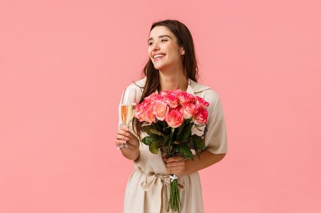 Concept d'élégance, de romance et de la saint-valentin. femme fête son anniversaire, s'amuser, profiter de la fête, tenant un verre de champagne, boire et rire, recevoir de belles fleurs en bouquet
