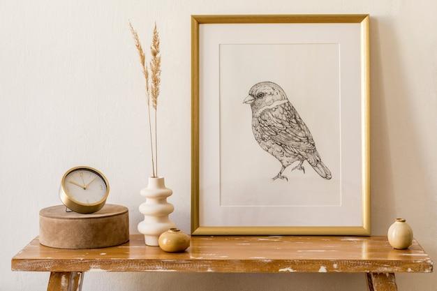 Concept élégant à l'intérieur du salon avec cadre en or, banc en bois, boîtes, fleurs séchées dans un vase, mur blanc et accessoires personnels élégants dans un décor moderne.