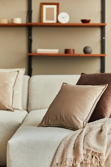 Concept élégant d'intérieur de salon avec canapé design beige, oreillers marron, bardeaux en bois, décoration et accessoires personnels élégants.