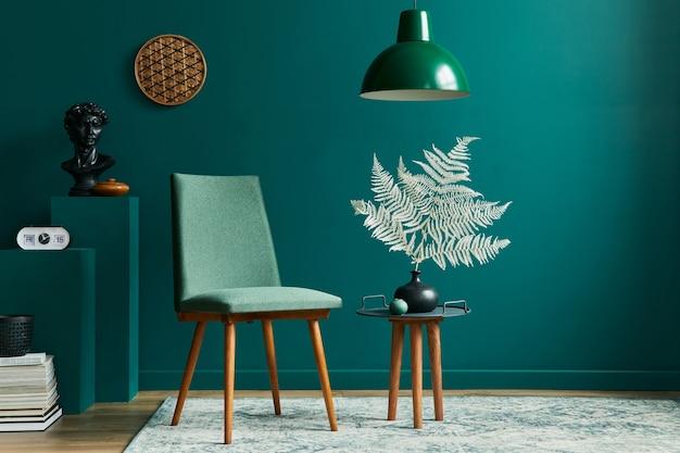 Concept élégant d'intérieur de salon avec petite table, chaises design, feuille séchée dans un vase beige, horloge, tapis rétro, décoration et accessoires dans une décoration d'intérieur vintage moderne