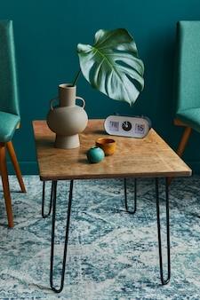Concept élégant d'intérieur de salon avec petite table en noyer, chaises design, feuille tropicale dans un vase beige, horloge, tapis rétro, décoration et accessoires dans une décoration vintage moderne