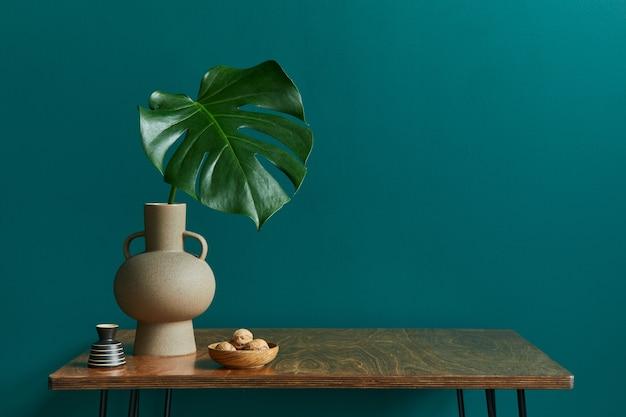 Concept élégant d'intérieur de salon avec table en noyer, feuille tropicale dans un vase, horloge et accessoires personnels élégants dans une décoration vintage moderne