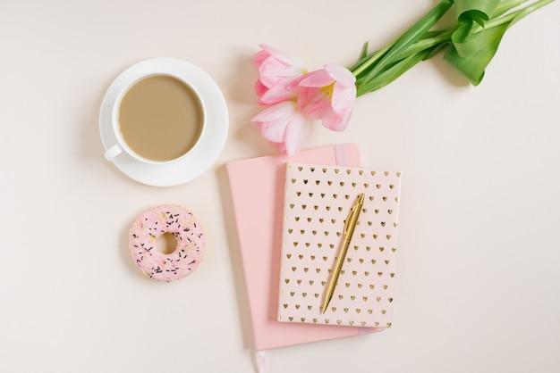 Concept élégant et tendance pour une blogueuse, pigiste : journal rose, cahier, donat, tulipes roses et une tasse de café sur fond beige. travail à domicile