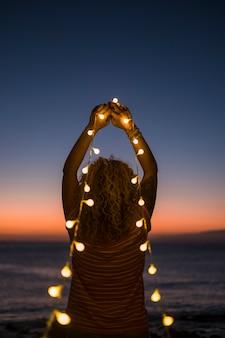 Concept émotionnel d'espoir et de foi avec femme adulte et lumières ampoule jaune défocalisé